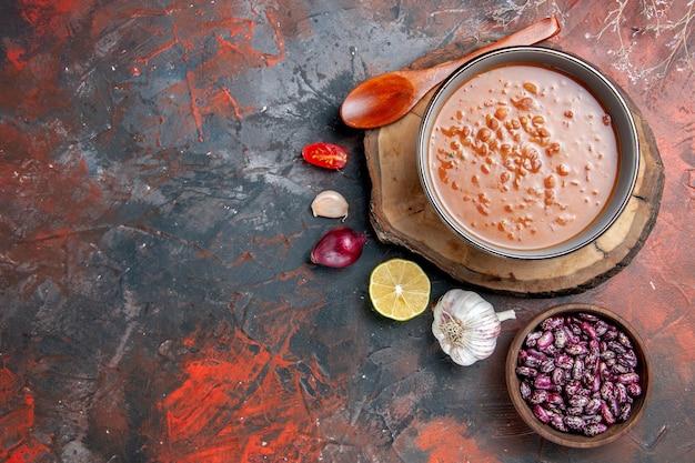 木製トレイ豆にんにくタマネギトマトとレモンの混合色のテーブルに青いボウルにスプーンで古典的なトマトスープのビューの上に