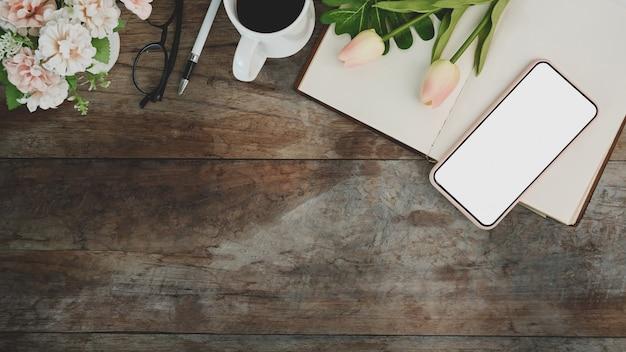 Выше вид удобного рабочего места со смартфоном, ноутбуком, кофейной чашкой и цветами на деревянном столе.