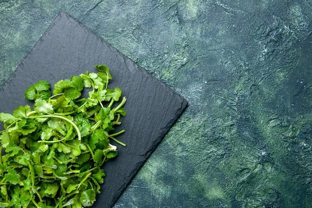 空きスペースのある緑と黒の混合色のテーブルの右側にある木製のまな板のコリアンダーバンドルのビューの上