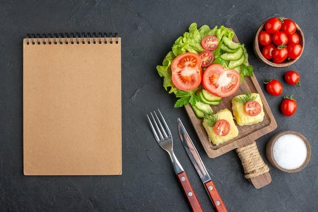 Выше вид нарезанных свежих помидоров и огурцов, сыра на деревянной доске, набор столовых приборов, солевой блокнот на черной поверхности