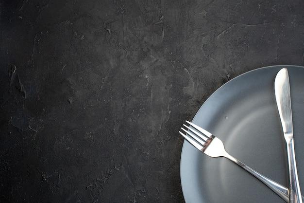 여유 공간이 있는 어두운 색 배경의 흰색 수건에 검정 접시에 설정된 칼 붙이 보기 위