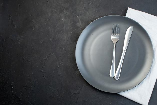 여유 공간이 있는 어두운 색 배경의 왼쪽에 있는 흰색 수건에 검정 접시에 설정된 칼 붙이 보기 위