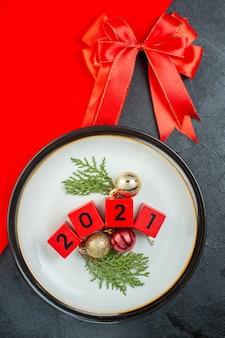 Выше вид номеров аксессуаров украшения на тарелке и красной ленте на темном столе