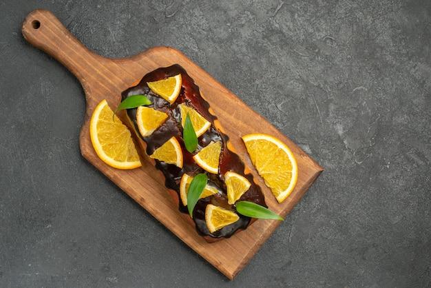 블랙 테이블에 커팅 보드에 오렌지와 초콜릿으로 장식 된 맛있는 케이크 위의보기