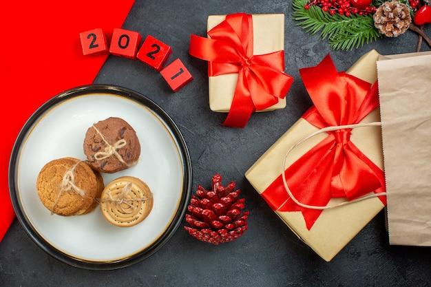 Выше вид вкусных кексов на тарелке хвойных шишек еловых веток с номерами красивых подарков на темном столе