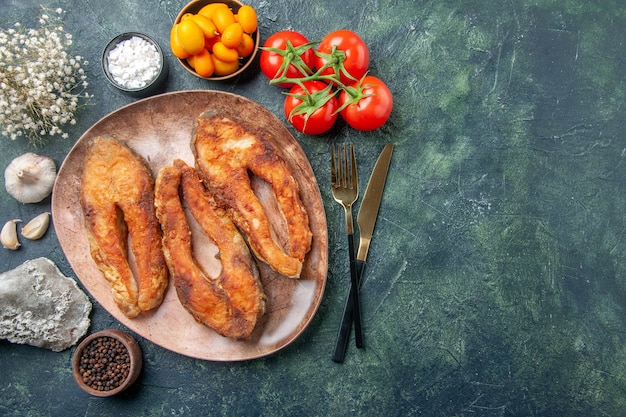 茶色のプレートとカトラリーセットのおいしい揚げ魚のビューの上に空きスペースのあるミックスカラーテーブルにスパイス食品を設定します