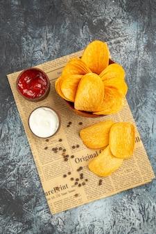 회색 테이블에 신문에 맛있는 수제 칩과 후추 그릇 마요네즈 케첩의보기 위