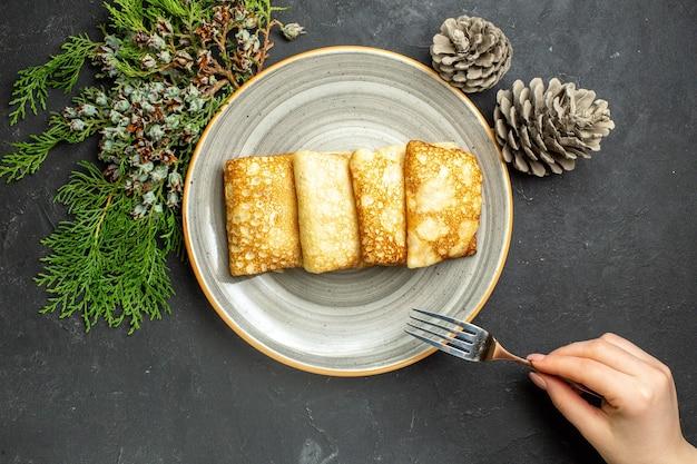 하얀 접시에 맛있는 고기로 가득 찬 팬케이크와 검은 배경에 침엽수 원뿔의 보기
