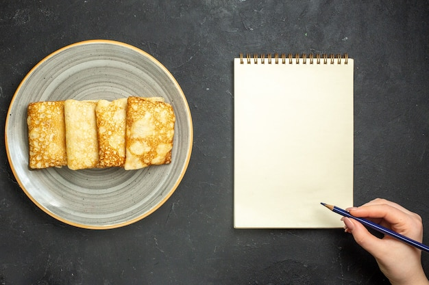 Выше вид вкусных блинов с мясной начинкой на белой тарелке и записной книжке на черном фоне