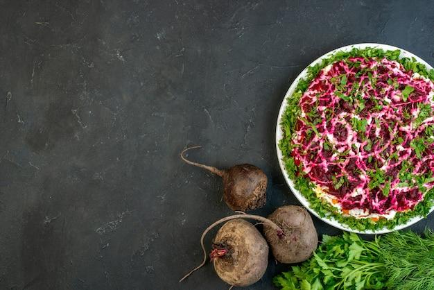 Выше вид вкусного салата в белой тарелке свекольного зеленого пучка на черном фоне со свободным пространством