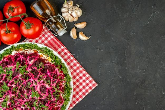 Выше вид вкусного салата на красном полосатом полотенце и упавшая бутылка масла из свежих овощей с правой стороны на черном фоне