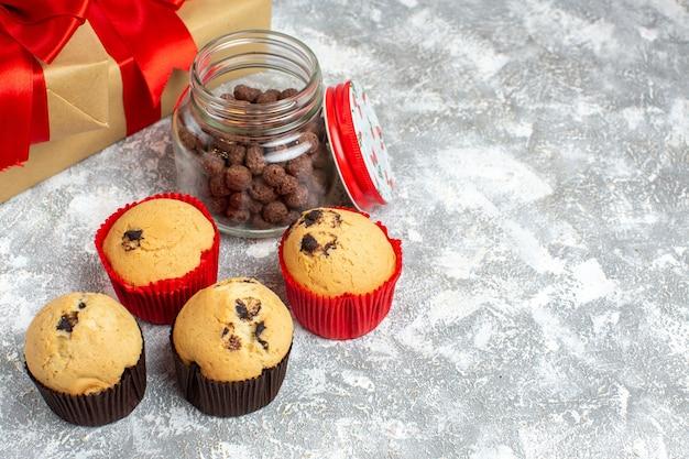 얼음 표면에 빨간 리본이 달린 선물 옆에 유리 냄비와 전나무 가지에 맛있는 작은 컵 케이크와 초콜릿보기 위