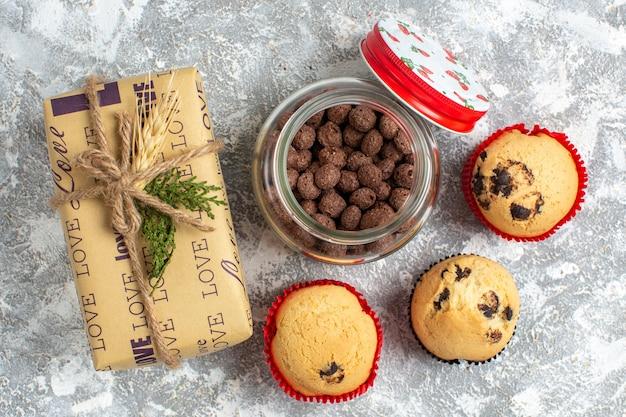 氷の表面のクリスマスプレゼントの横にあるガラスの鍋においしい小さなカップケーキとチョコレートのビューの上
