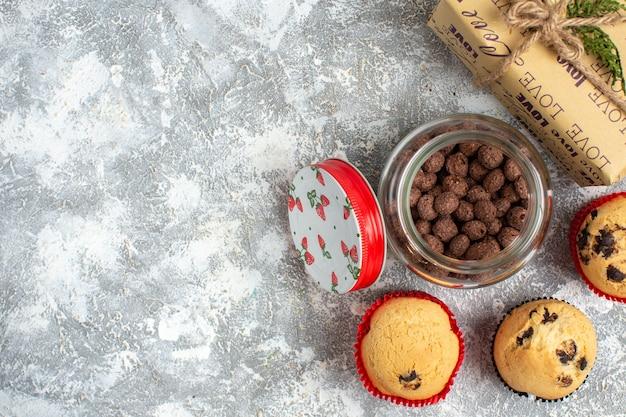 Вверху вид на вкусные маленькие кексы и шоколад в стеклянной кастрюле рядом с рождественским подарком слева на поверхности льда.