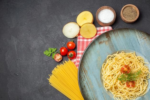 Выше вид вкусных спагетти, подаваемых с помидорами, зеленью и разными специями, сырыми макаронами на красном полосатом полотенце на черном фоне