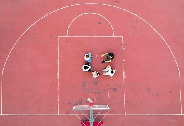 낮에 코트에 서있는 농구 선수의 위 모습