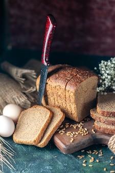 Выше вид диетического черного хлеба на деревянной разделочной доске, нож, цветок, яйца, мука в миске, коричневое полотенце на фоне смешанных цветов
