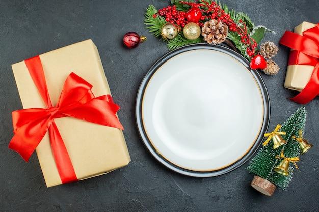 ディナープレートのビューの上に黒い背景に赤いリボンとクリスマスツリーモミの枝針葉樹の円錐形のギフトボックス