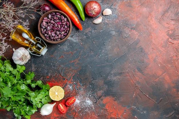 混合色のテーブルに食べ物と豆の落ちたオイルボトルと緑のレモントマトの束で夕食の準備のビューの上に
