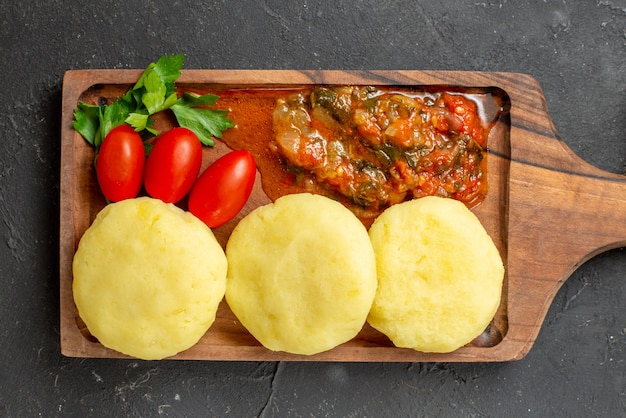 Вид сверху на приготовление ужина с сырыми овощами на коричневой разделочной доске