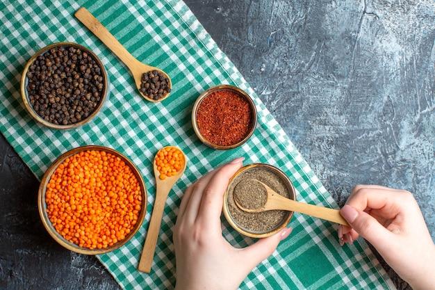 灰色の背景に緑の剥ぎ取ったタオルの上に、さまざまなピーマンと黄色いエンドウ豆を使った夕食の準備のビューの上