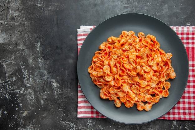 赤い皮をむいた布の黒い皿の上にある、夕食の簡単なパスタ料理