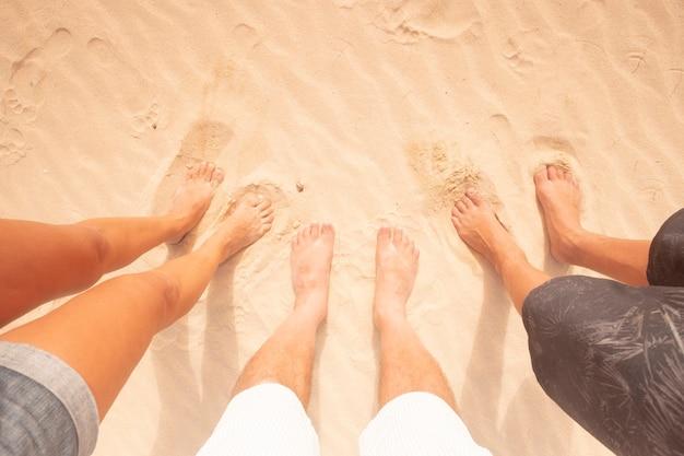 夏休みにビーチを一緒に楽しんでいる家族の足の上のビュー