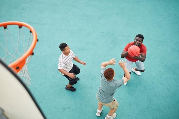 Выше вид отца, бросающего баскетбол в обруч во время игры с сыновьями на спортивной площадке