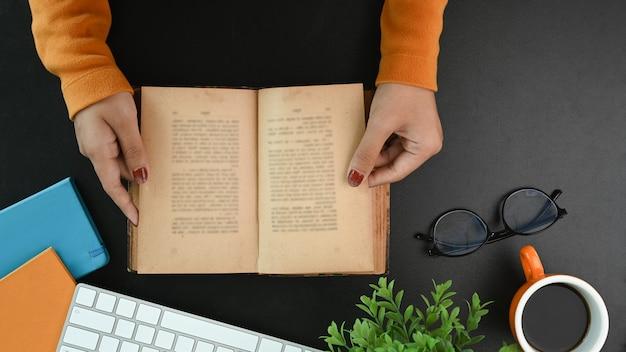 Выше взгляд студентки женского колледжа, читающей книгу на черном столе.
