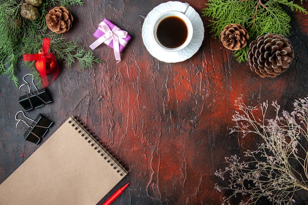モミの枝のビューの上に暗いテーブルの上のペンでノートの横に紅茶の装飾アクセサリーとギフトのカップ