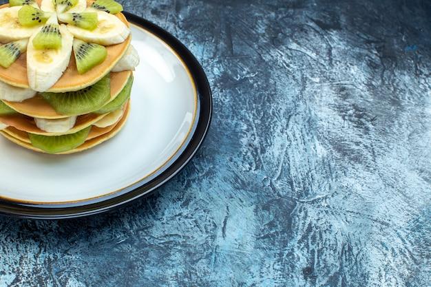 천연 요거트로 만든 푹신한 미국식 팬케이크와 여유 공간이 있는 얼음 배경의 오른쪽 접시에 과일 겹겹이 쌓인 모습