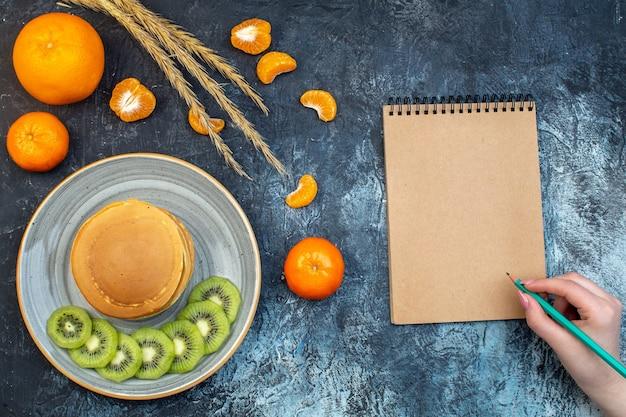 자연 요구르트로 만든 푹신한 미국식 팬케이크가 접시에 키위 과일과 귤과 함께 제공되고 여유 공간이 있는 얼음 배경에 펜 온노트북을 들고 있는 모습