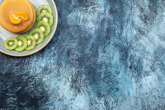 천연 요구르트로 만든 푹신한 미국식 팬케이크가 얼음 배경 위에 있는 접시에 오른쪽에 키위 과일과 함께 제공됩니다.