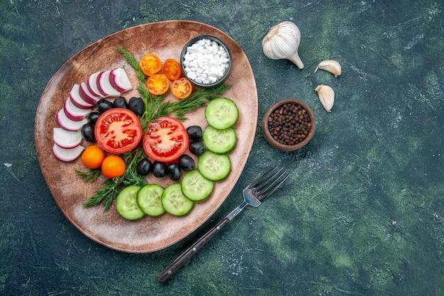茶色のプレートに新鮮なみじん切り野菜オリーブと緑黒の混合色のテーブルにフォークペッパーニンニクのビューの上 無料写真