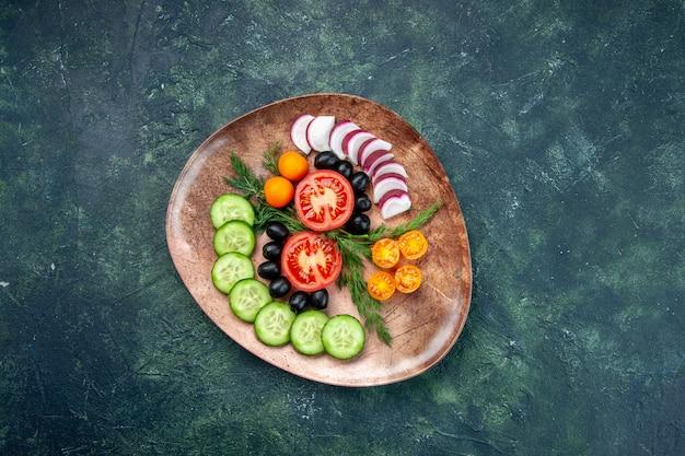 Выше вид свежих нарезанных овощей кумкватов оливок в коричневой тарелке на зеленом черном столе смешанных цветов