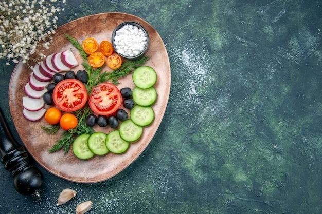 Выше вид свежих нарезанных овощей, оливок, солей в коричневой тарелке и кухонного молотка с правой стороны на зеленом черном столе смешанных цветов