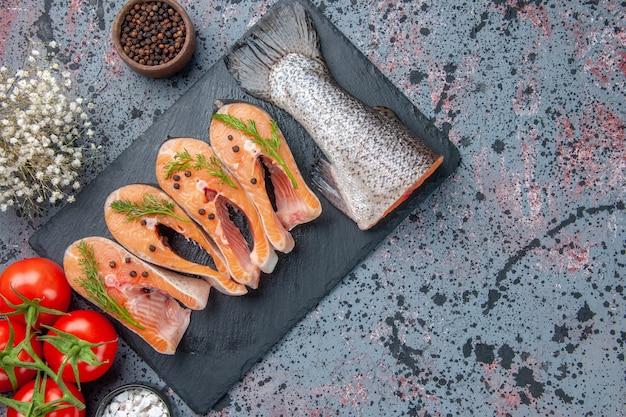 新鮮なカットの生の魚の緑の暗い色のトレイのスパイス、青黒のミックスカラーテーブル、空きスペース