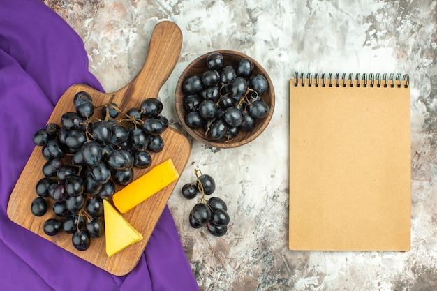 나무 커팅 보드에 있는 신선하고 맛있는 검은 포도 다발과 치즈의 보기