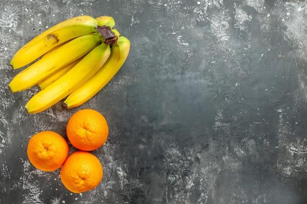 오른쪽 어두운 배경에 있는 신선한 오렌지와 천연 유기농 바나나 번들의 보기