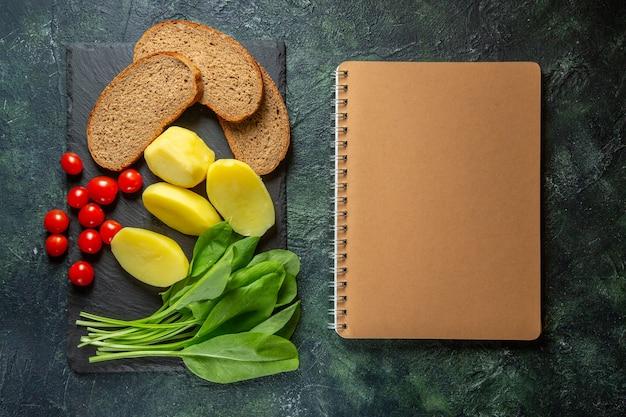 Выше вид свежего очищенного нарезанного картофеля и диетических ломтиков хлеба, помидоров, зеленая пачка на деревянной разделочной доске, спиральный блокнот на поверхности зеленого и черного цветов