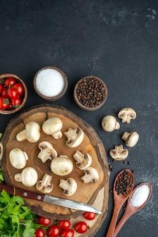 Выше вид свежих сырых грибов и зеленых специй, помидоров, ножей, на деревянной доске, полотенце на черном фоне