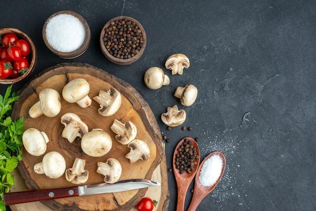 검은 배경에 있는 나무 판자에 있는 신선한 생 버섯과 칼 토마토 향신료의 보기