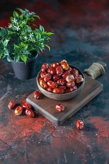 나무 커팅 보드에 있는 그릇에 있는 신선한 생 은베리 과일과 혼합 색상 배경의 화분