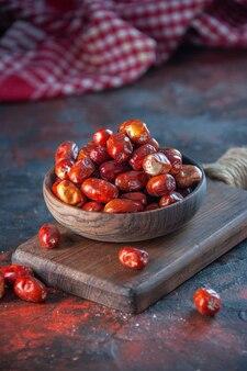 혼합 색상 배경의 나무 커팅 보드에 있는 그릇에 있는 신선한 생 은베리 과일의 보기