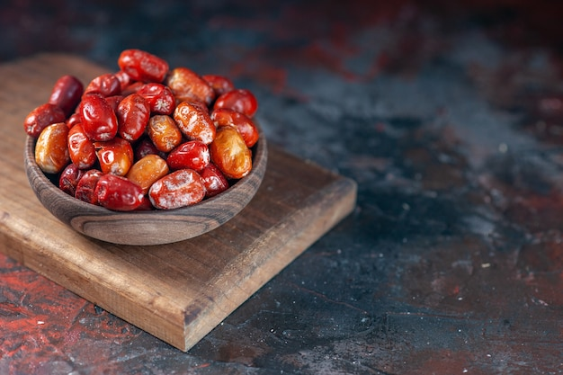 혼합 색상 배경의 나무 판자에 있는 작은 그릇에 있는 신선한 생 은베리 과일의 보기