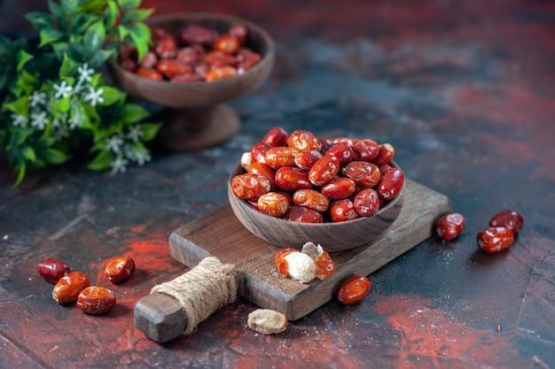 도마 위의 나무 그릇에 있는 신선한 생 은베리 과일과 혼합 색상 배경의 화분