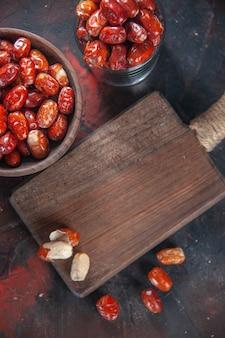 그릇에 있는 신선한 생 은베리 과일과 혼합 색상 배경의 나무 커팅 보드 위에 있는 보기