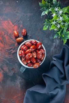 회색 컵 내부와 외부의 신선한 생 은베리 과일과 혼합 색상 배경의 화분 짙은 색 수건
