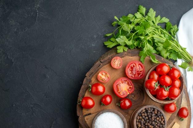 黒い表面の左側にある木の板に、ボウルに入れた新鮮なトマトとスパイスのスプーンのビューの上