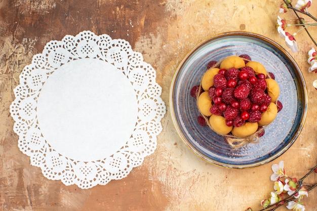 Выше вид свежеиспеченного мягкого торта с фруктами, цветами и салфеткой на столе смешанных цветов